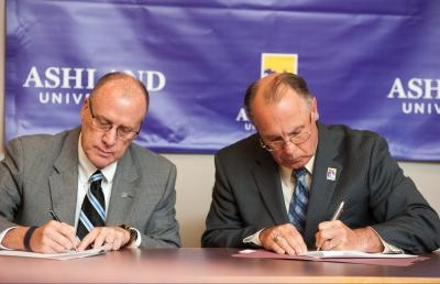 Ashland University Provost Dr. Frank Pettigrew (right) and Tim Shaw, vice president of Strategic Development and director of education at Advanced Technical Intelligence Center (ATIC), sign partnership papers at a news conference on July 10.