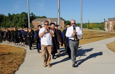 Music professors Tom Reed (r) and Scott Garlock lead the Ceremonial Walk to the new Dwight Schar College of Nursing.